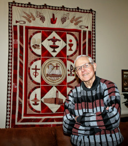 picture by Barb Arland-Fye Father Mike Volkmer, C.PP.S., treasures this handmade quilt given to him years ago by parishioners of St. Mary Parish in Centerville where he had served. The quilt features symbols of his religious community, Missionaries of the Precious Blood.