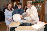 Fr. Matt Link baptises a child into the Catholic faith