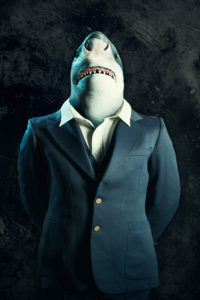 A great white shark in a business suit stands for a portrait, his hands crossed behind his back.  Conceptual depiction of a loan shark, or other predatory lending business practices in the corporate world.
