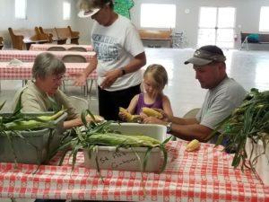 People peeling corn